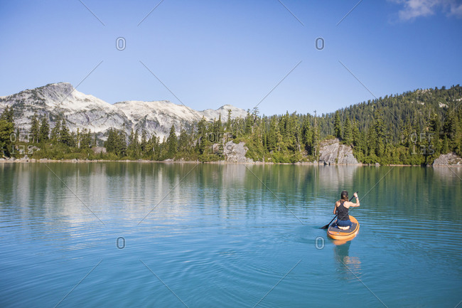 Attractive woman paddles Stand up paddle board on blue lake.