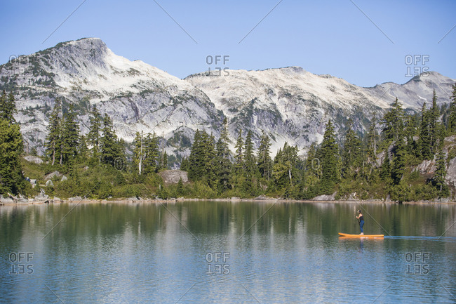 Side view of active woman paddle boarding on mountain lake.