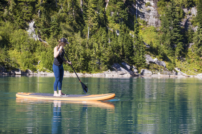 Young woman paddle boarding on remote lake.