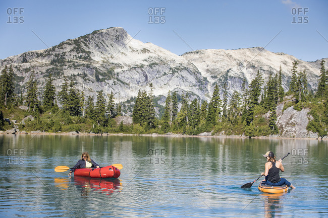 Mother and daughter paddling on remote lake in the mountains.