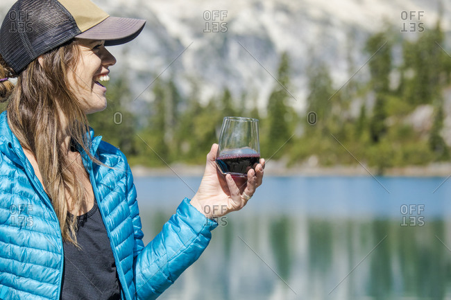 Young active attractive woman enjoys red wine at the lake.