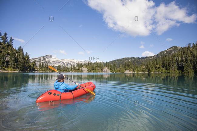 Active man paddling on remote lake, B.C., Canada.