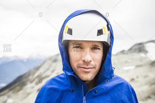Portrait of mountain climber wearing helmet and rain jacket.