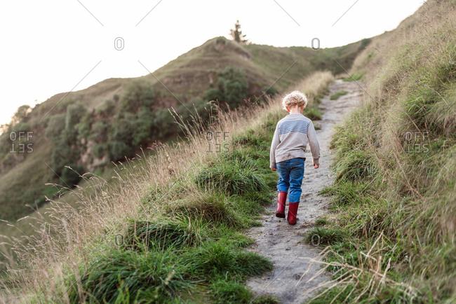 Preschool aged child walking on hillside path