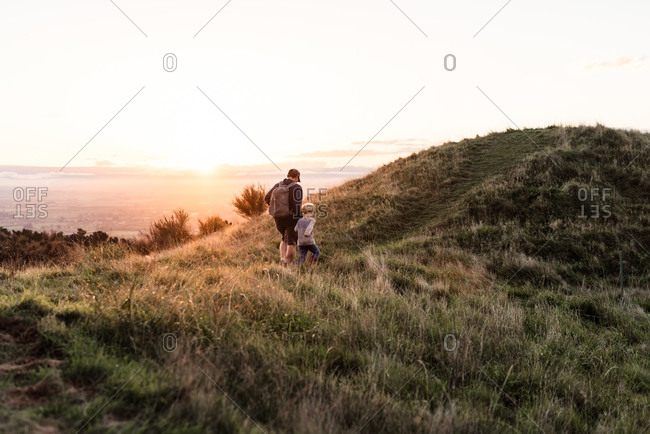 Father and son walking on hillside at dusk