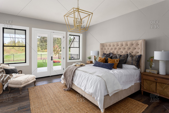 Master bedroom interior in new luxury home. French doors lead outside