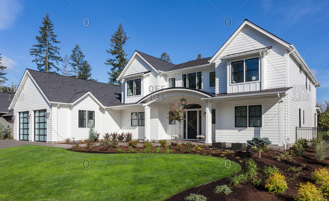 Beautiful modern farmhouse style luxury home exterior with blue sky