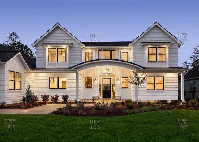 Beautiful modern farmhouse style luxury home exterior at twilight