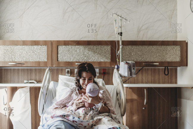 Mid view of mother in hospital bed looking at newborn son