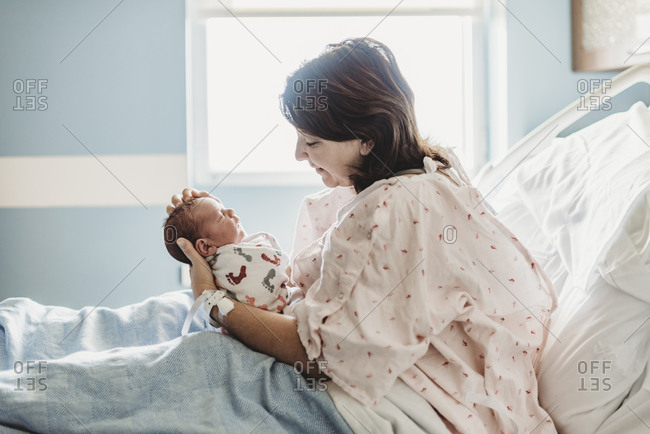 Side view of mother looking lovingly at newborn son in hospital