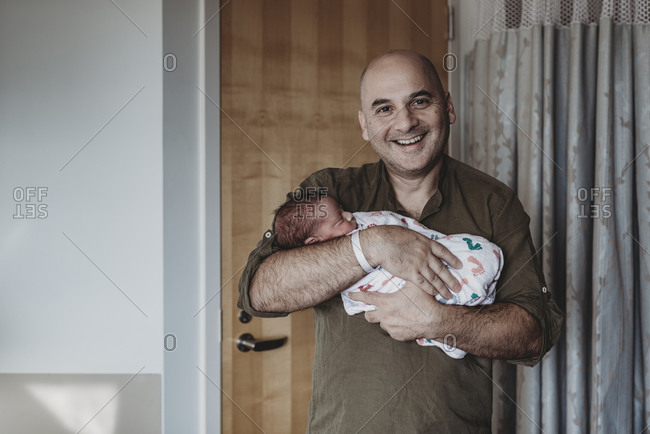 Father holding newborn boy wrapped in blankets in hospital