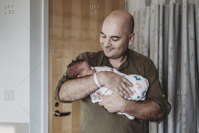 Happy father holding newborn boy wrapped in blankets in hospital