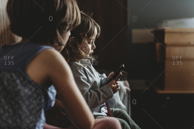 Side view of young boy playing on phone in hospital