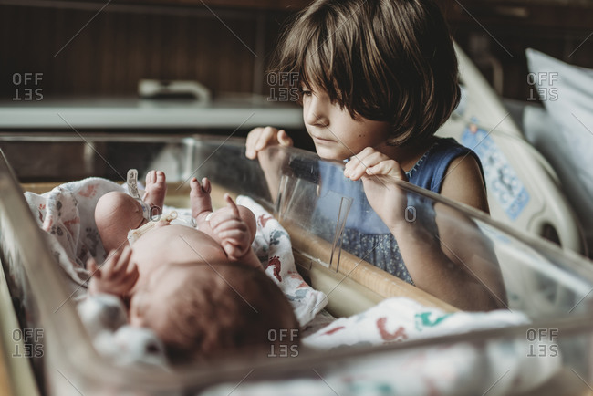 Sister looking at newborn brother in hospital bassinet