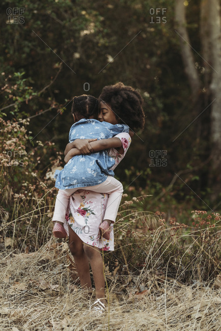 Portrait of two sisters hugging in backlit field