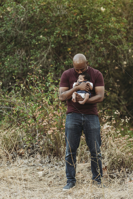 Portrait of happy father holding newborn age daughter in backlit field