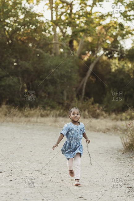 Preschool-aged girl running confidently in field