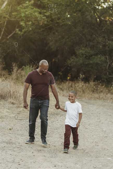 Happy father and son holding hands and walking in field