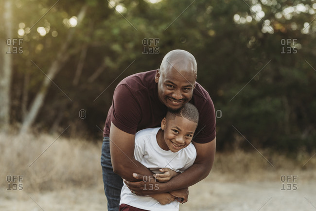 Close up of happy father and son hugging in backlit field