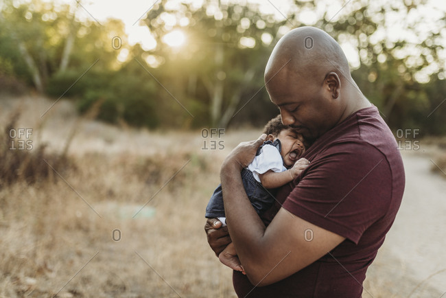 Close up of sweet father cuddling newborn girl in backlit field