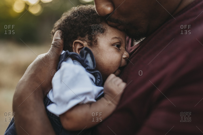 Close up of sweet father kissing newborn girl in backlit field