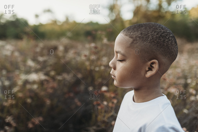 Side view of serious school-aged boy closing eyes in flower field