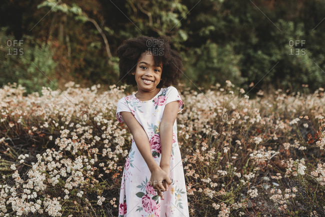 Portrait of young school-aged girl smiling in field of flowers