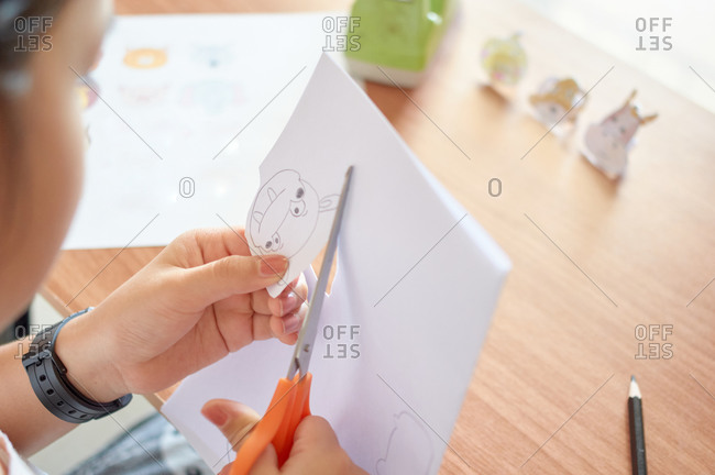 A girl is cutting paper for making crafts.