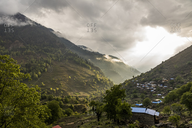 Landscape of green mountain valley and village at sunset in Nepal