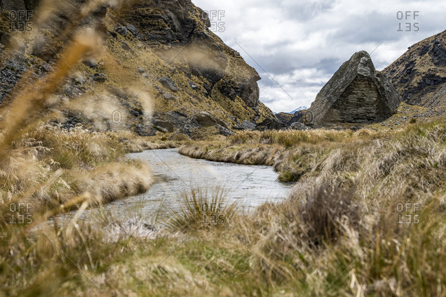 Rugged alpine landscape with a stream and rocks in New Zealand