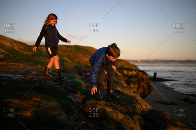 Happy siblings climbing on rocks at sunset near the ocean