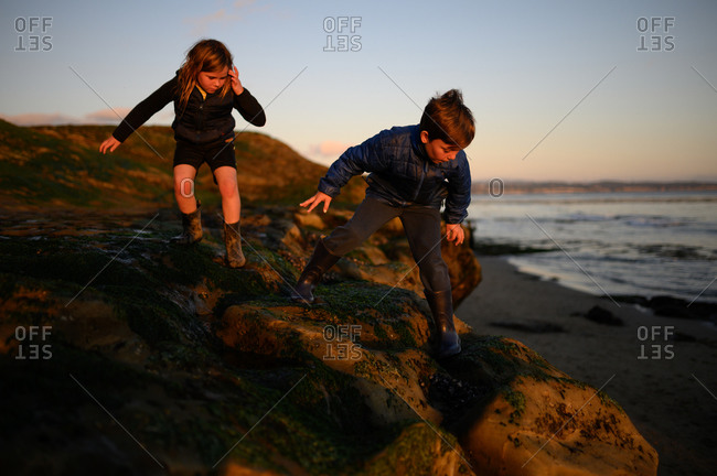 Siblings climbing down rocks near the ocean at low tide and sunset