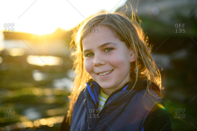 Backlit sunset portrait of long haired boy smiling at the camera
