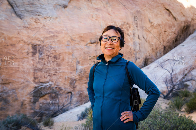 Portrait of Smiling Senior Asian Woman hiking in the desert landscape