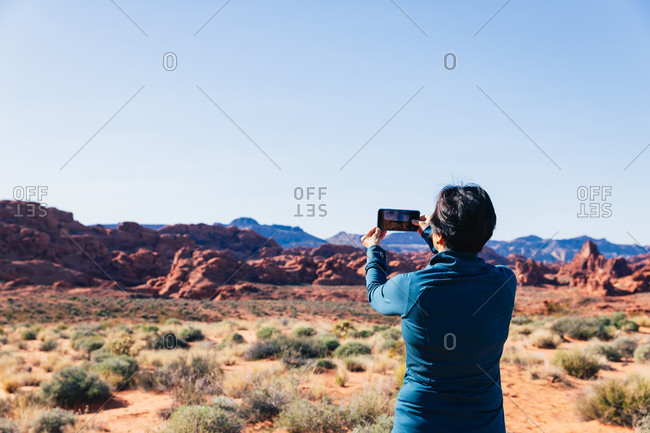 Senior Asian woman taking a photo of a desert landscape with her camer