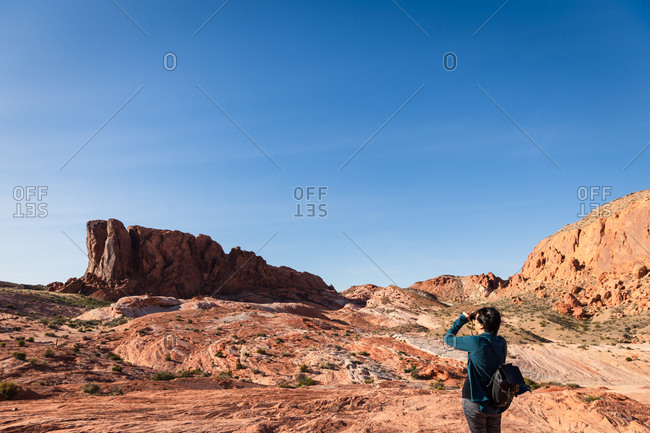 Woman Looking with binoculars out into the desert landscape