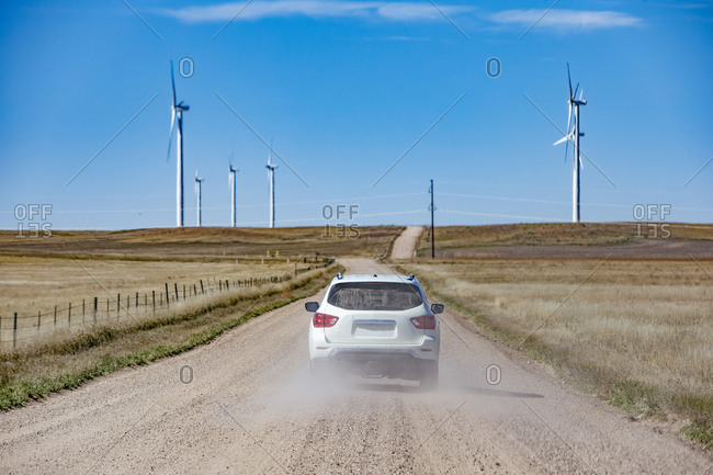 Wind Turbines in Colorado against blue sky with car