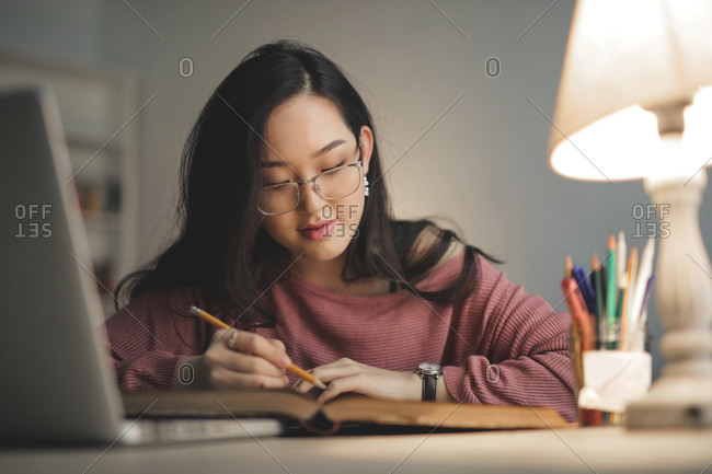 Young asian woman studying at home
