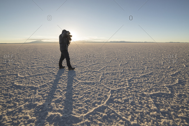 man photographing Irregular structures of salt at sunrise