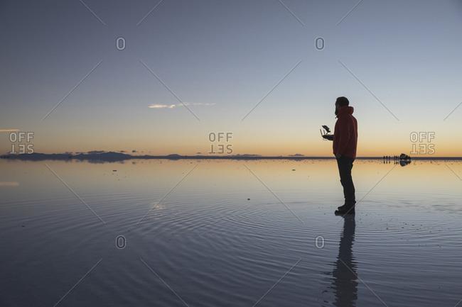 man driving drone over water in uyuni salar