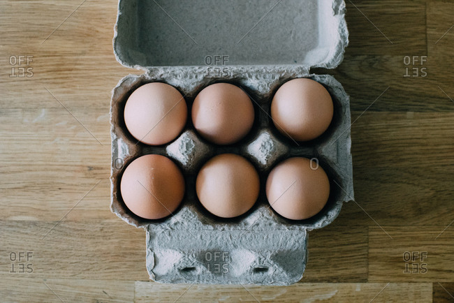 a bunch of eggs sit in a carton on a table during the day