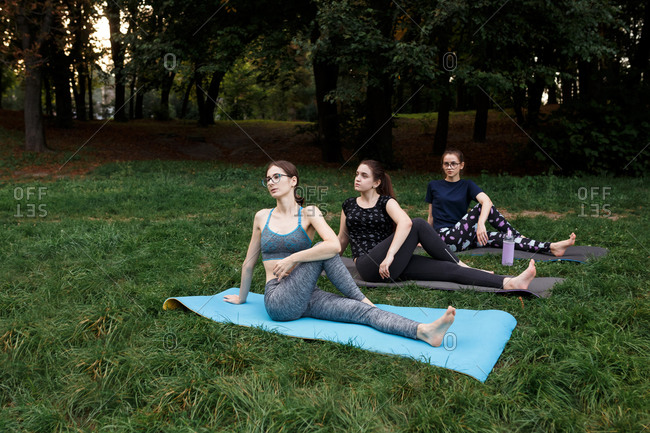 The relaxed girls is doing yoga in the park on carpet