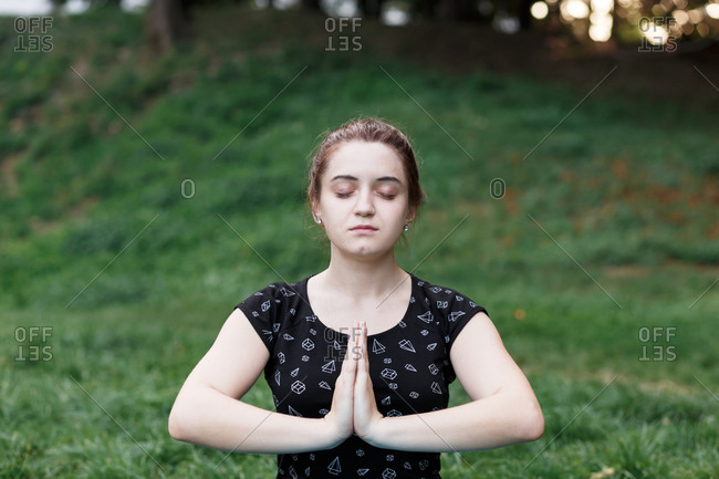 The relaxed girl is doing yoga in the park on carpet