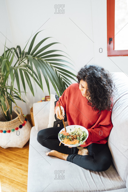 Brunette woman eating a healthy green salad.