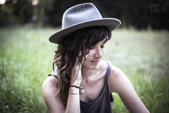 natural girl with freckles and tattoos sits peacefully in long grass