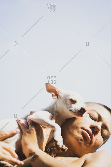 artistic crop on beautiful strong asian woman cuddling small puppy sun