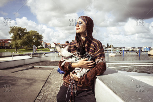strong woman in sun glasses by boats holds two dogs in sunlight