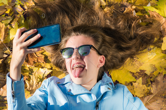teenager girl wearing sunglasses and lying down on the floor covered by yellow leaves while taking a photo with her mobile phone to herself. The girl is smiling and showing her tongue to the