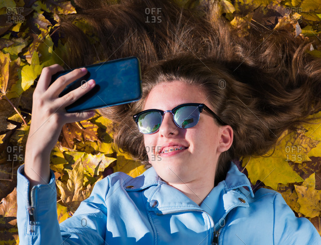 Teenager girl wearing sunglasses and lying down on the floor covered by yellow leaves while taking a photo with her mobile phone to herself. The girl is smiling to the camera. Horizontal phot