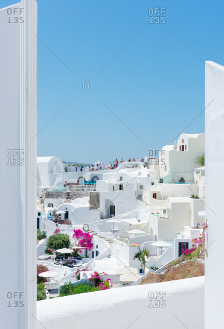 amazing panoramic view through a gate of some white houses of the village of touristic Oia in Santorini island in Aegean sea. Many tourists at the back are visiting a spectacular place. Verti